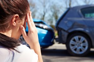Image of a woman holding her head after having an auto accident injury.